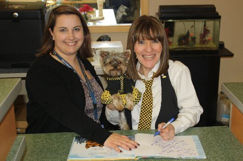 Author Elly & Schmitty The Weather Dog signing a book for the South End School library with Principal Nattrass.